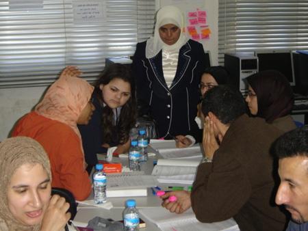 المدربة تستمع لنقاش بعض المجموعات و تراقب مدى تعلمهم من بعضهم البعض لأن التعلم من القرين هو الأفضل..