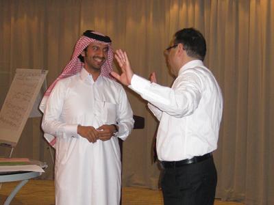 المدرب أحمد الخطيب يشير إلى المتدرب علي السويدي بضرورة إعادة صياغة الإجابة بكلماته الخاصة كشرط لقبولها في البرنامج التلفزيوني