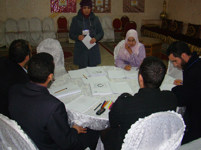 المتدربة حليمة الطلباوي تقدم عرضا أمام مجموعة من المتدربين تليه تعليقات المدربين والمتدربين.