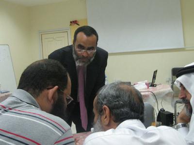 بعض المتدربين في حالة من الحوار والمناقشة أثناء الأنشطة والمدرب يتابع باهتمام.