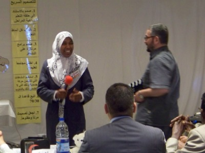 Trainee Mohammad Omran Almourabet is giving a sign to trainee Samia  Benseghierindicating the beginning of the presentation