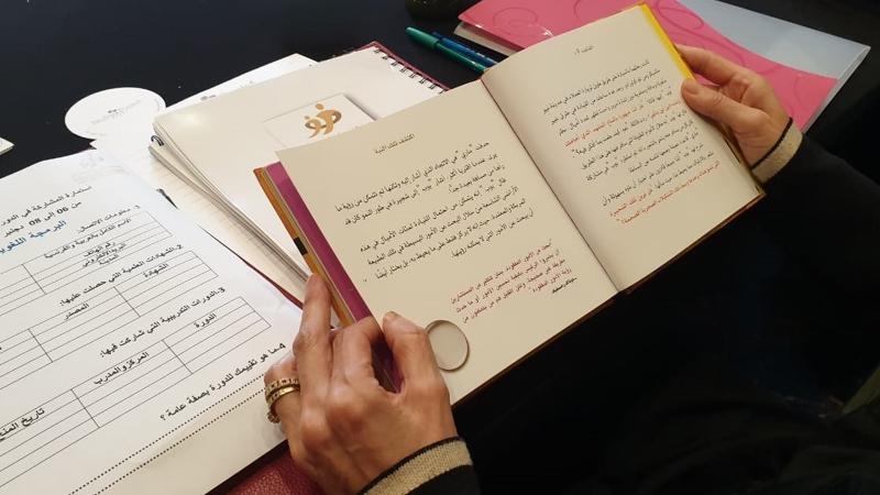 متدربة أثناء قراءة في كتيب الدورة