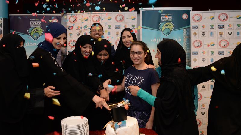 المشاركون في دورة دبلوم مدرب أول معتمد أثناء الاحتفال وتقطيع قالب كيك الدورة