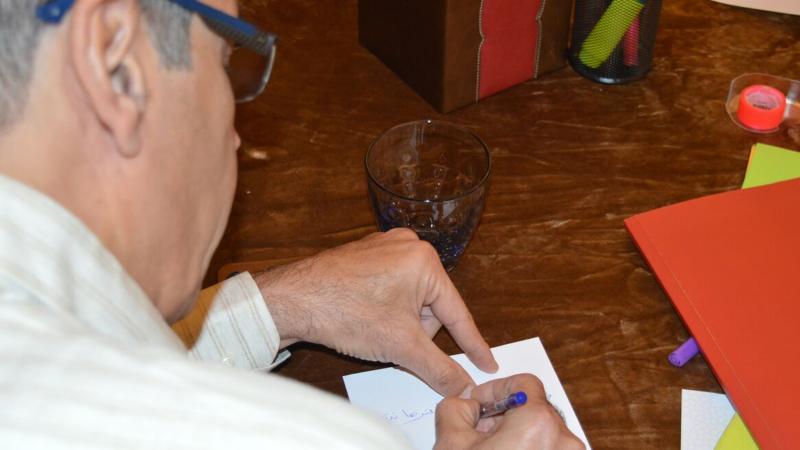 أحد المتدربين يكتب كلماته على البطاقات التي سيتم تبادلها مع المتدربين