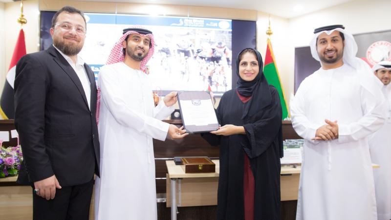 الدكتور محمد والمدرب الإعلامي فيصل والمدرب الخبير ماجد أثناء تقديم شهادة شكر وتقدير للسيدة  نورة الأنصاري